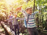 Happy kids hiking in a forest. Children are walking on a faller tree trunk, balancing with arms outstretched.