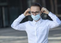 Beautiful business woman, young girl putting on medical protective mask on her face, in white shirt in glasses outdoors, healthcare at job, work, office. Coronavirus, virus, epidemic, covid-19 concept